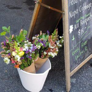 Multicolored bouquet in bucket near chalkboard sign