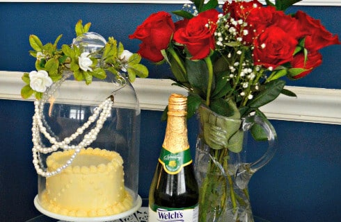Champagne and roses with a white caked encased in a pearl-draped glass dome.