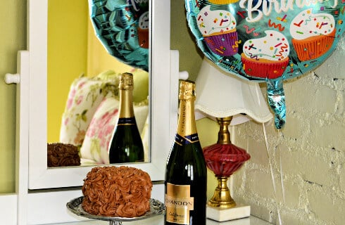 Small choclate cake with bottle of chanpagne and a Happy Birthday Balloon.
