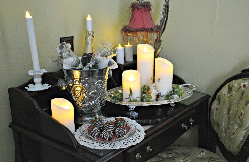 Side table in bedroom with candles, champagne in a silver bucket and chocolate covered strawberries.