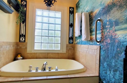 Two person whirlpool tub with garden mural wall and wrought iron fence