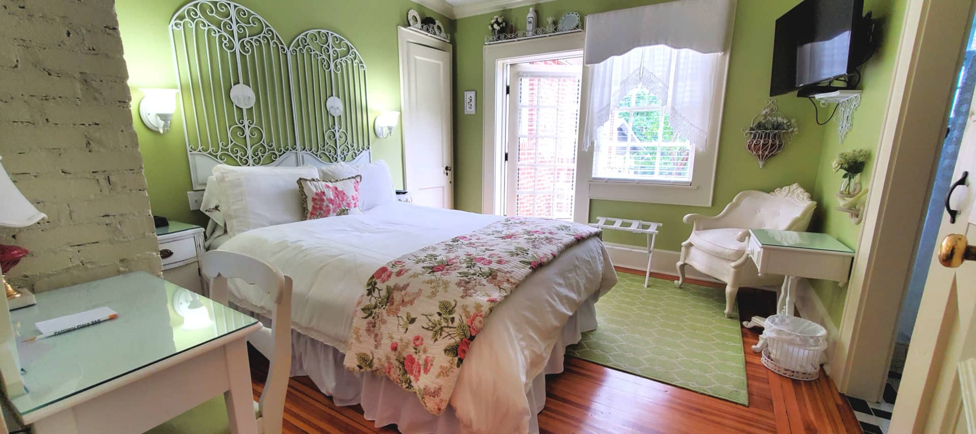 Guest room with queen bed, large screen television, desk and chair. Open patio door.