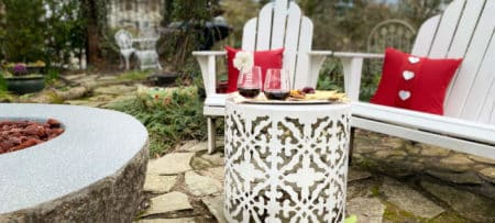 Wine and cheese tray in garden near white chairs and fire pit